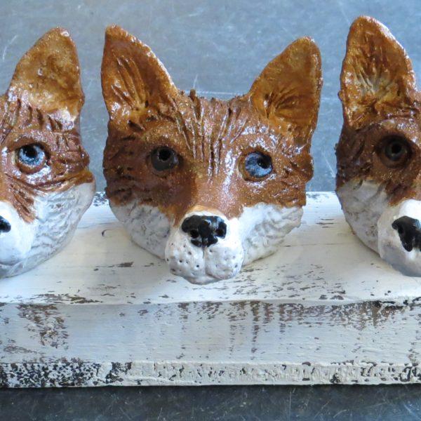 3 fox heads on woodblock